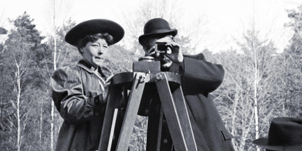 A black and white image of two people taking a photo