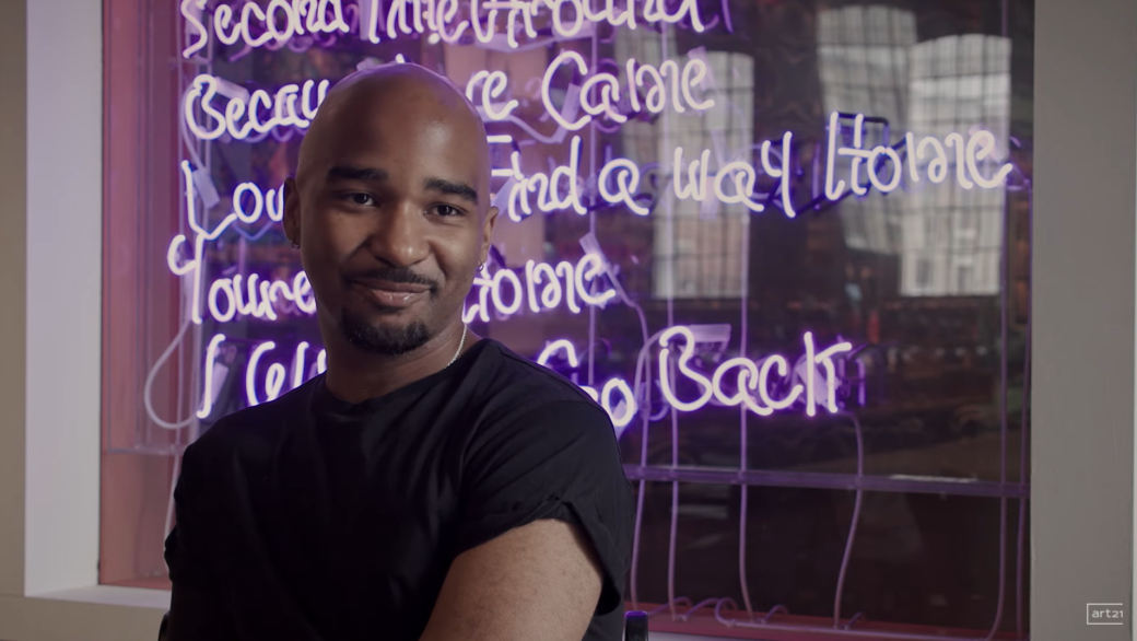 A smiling figure poses in front of a neon text sculpture lit in purple