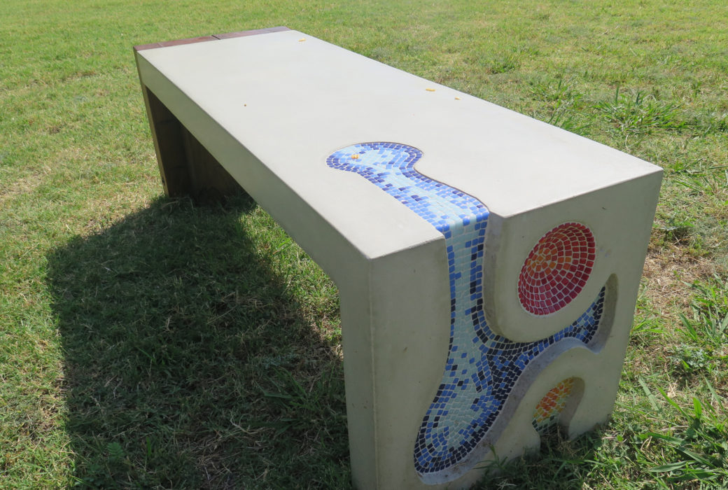 A concrete bench features curved and circular patterns filled with mosaic tiles
