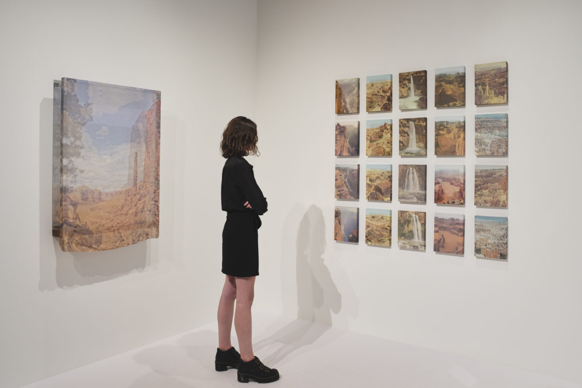 Woman standing in gallery looking at art on the wall