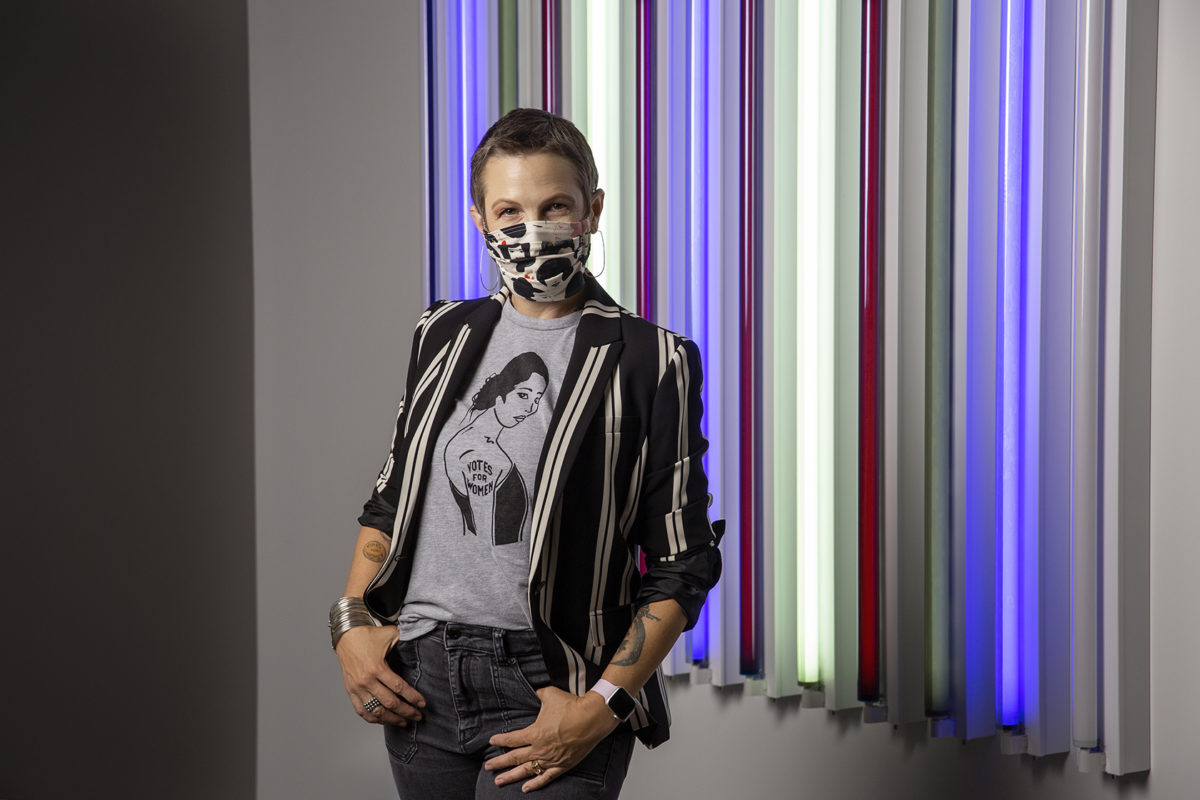 A figure in a mask stands in front of a light sculpture made of fluorescent tubes