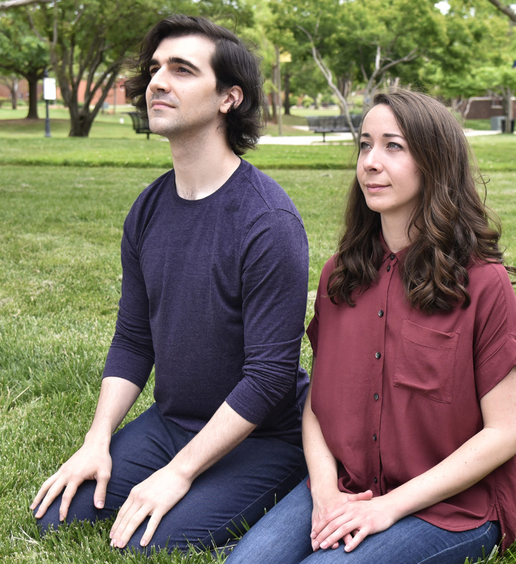 Two figures -- one in a blue shirt with short hair, one in a red shirt with long -- kneel in a grassy park