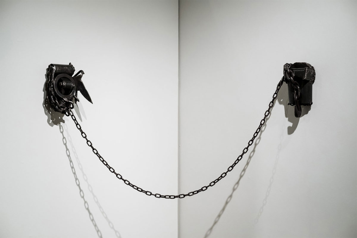 A sculpture of a black metal chain strung across two white walls that meet at the corner