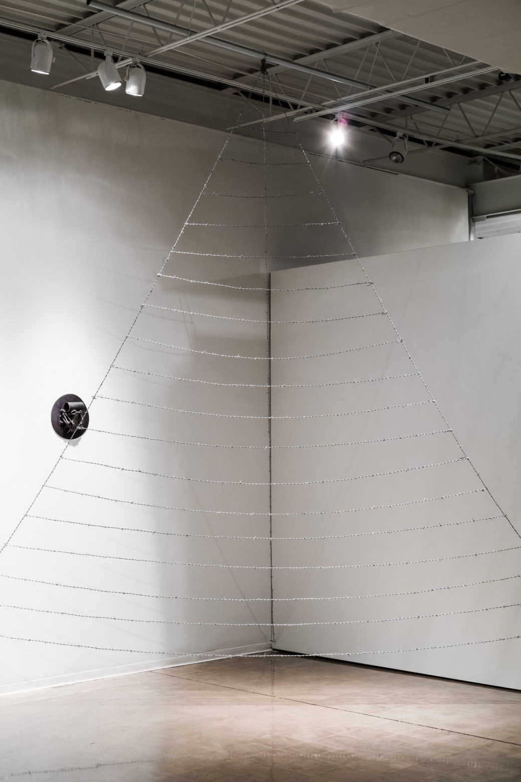 A sculpture of two wires hanging from the ceiling, forming a triangle with 19 horizontal pieces connected across