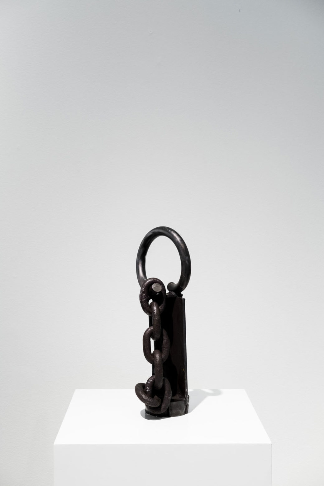 A small black sculpture made of steel sits on a pedestal in a gallery