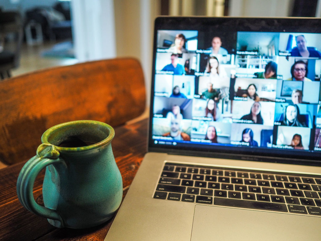A ceramic coffee mug sits next to a Macbook laptop, displaying a video chat interface including dozens of participants