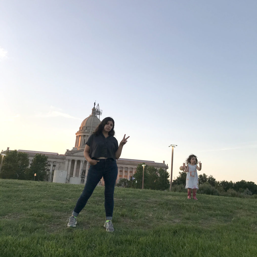 An adult and child flash peace signs in front of the Oklahoma State Capitol
