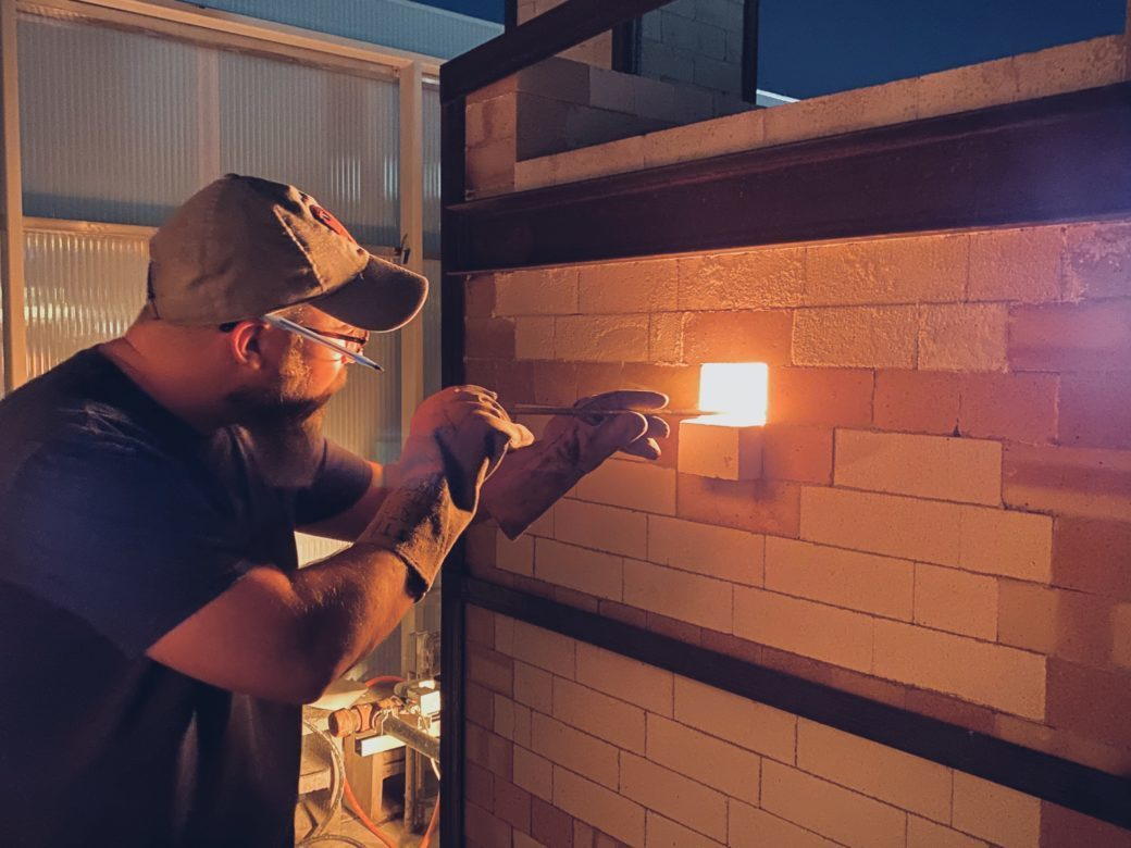 A figure inserts a tool through an opening in a ceramic kiln, with the light from the interior flame visible through the opening