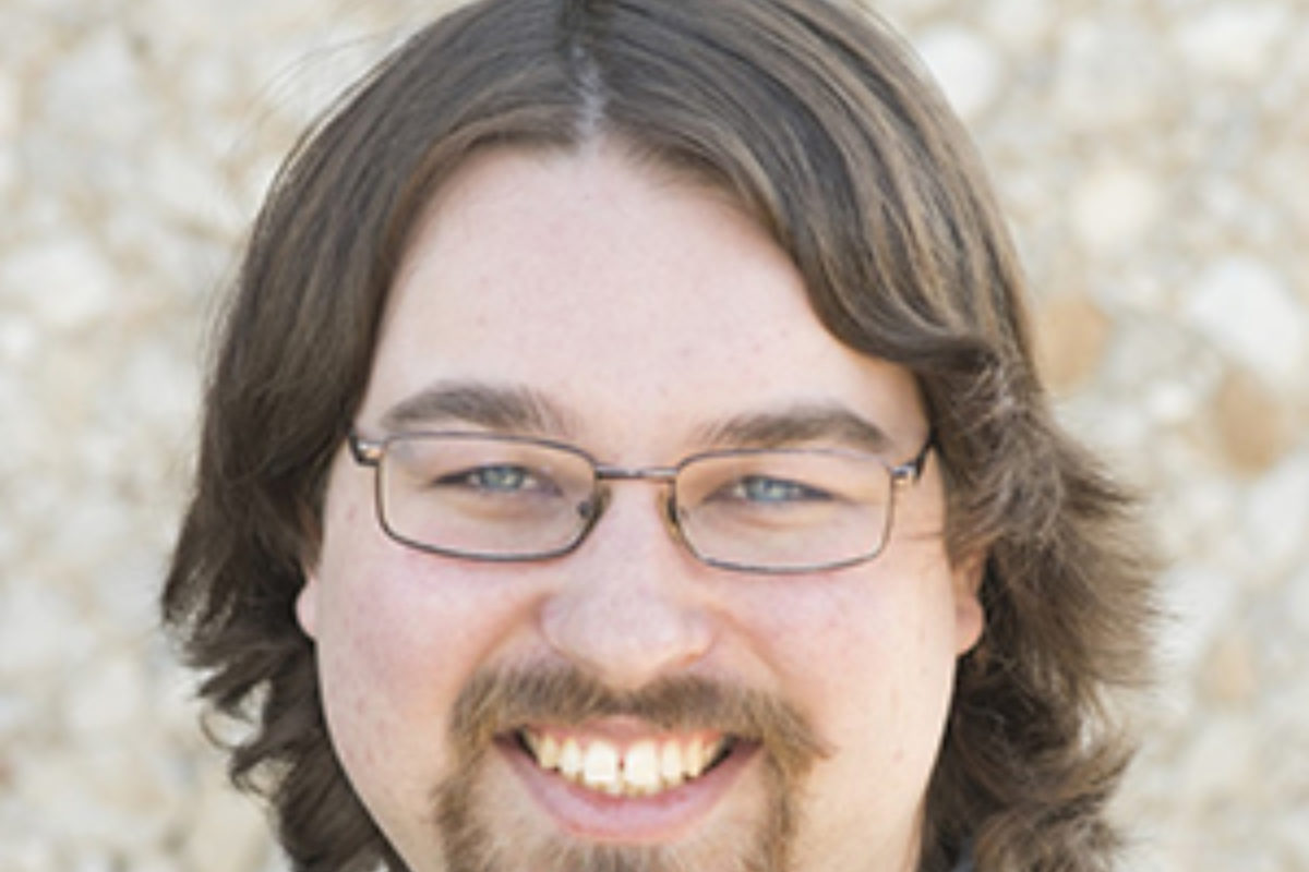 Color photo of a man with shoulder-length hair, glasses, and facial hair smiles at the camera.