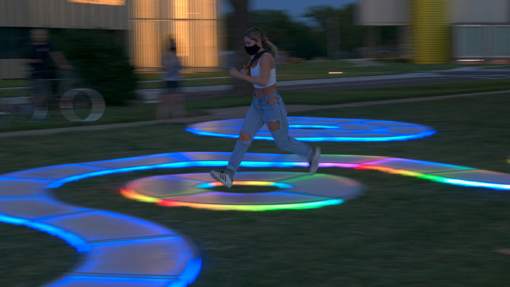 A figure plays on a winding LED-lit path in a park at dusk