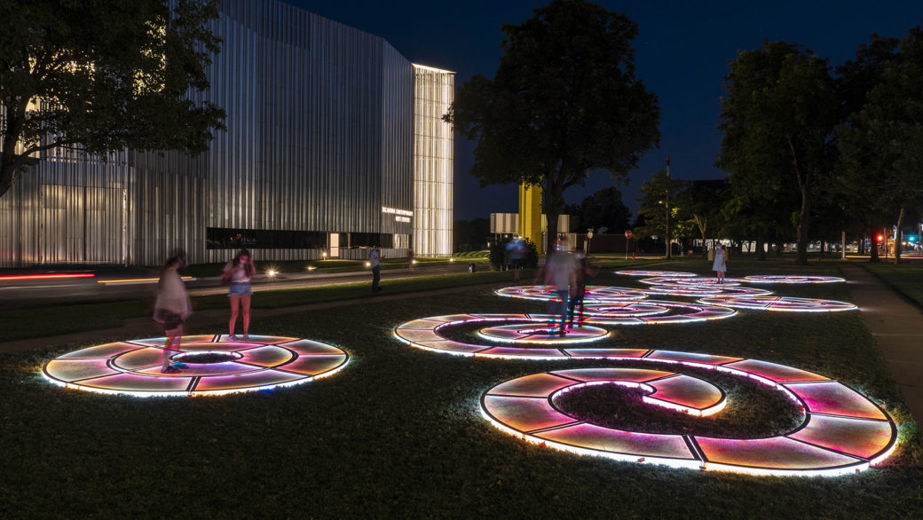 People play on a winding LED-lit path in a park after dark