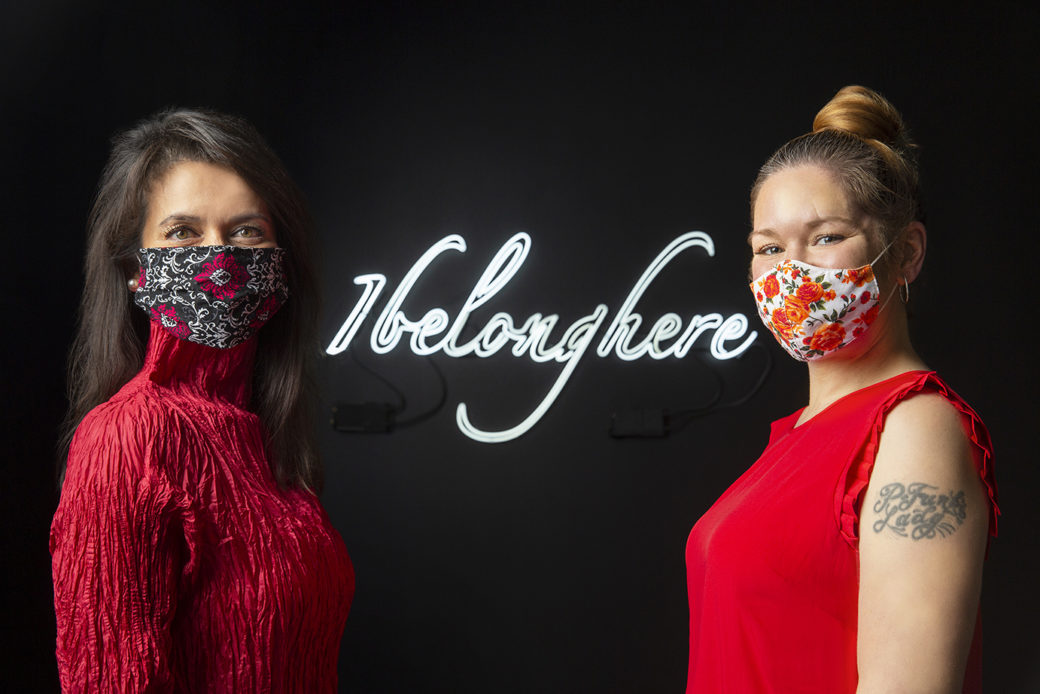 Two masked figures pose in front of a light sculpture depicting the following words: I belong here