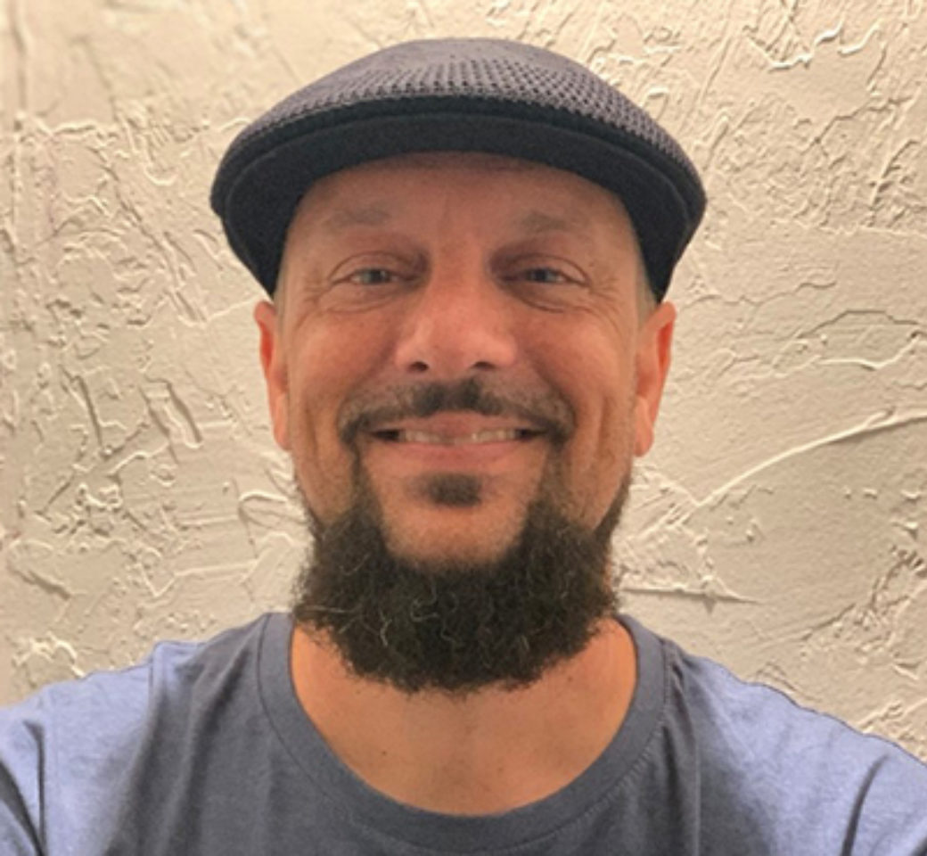Color photo of a man with a beard and flat hat smiles at the camera