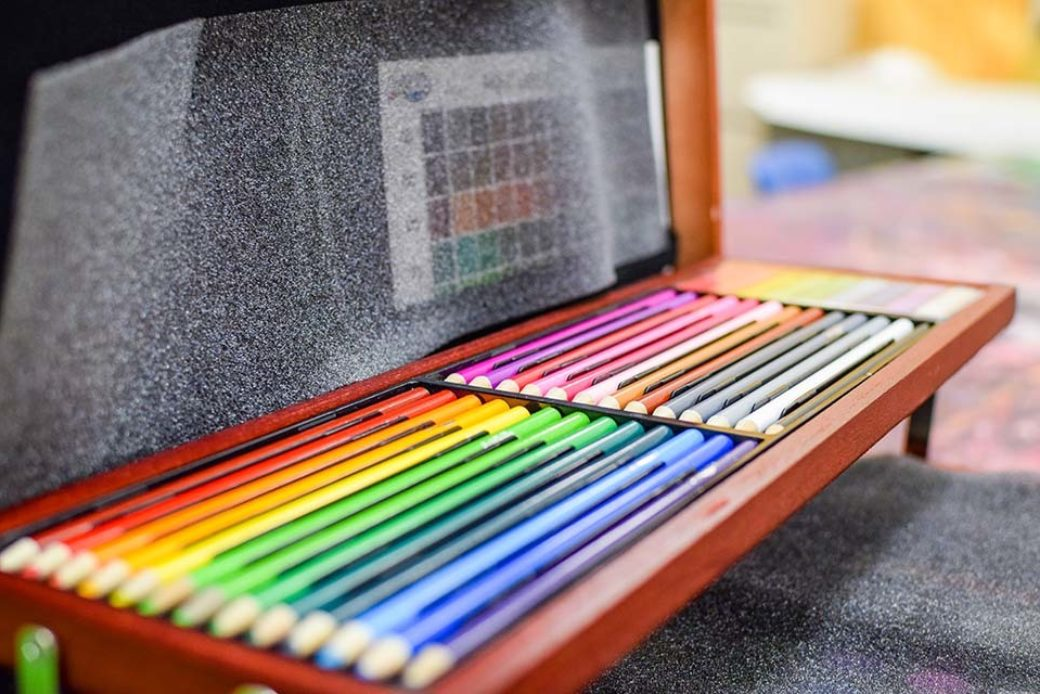 a box of colored pencils stands open