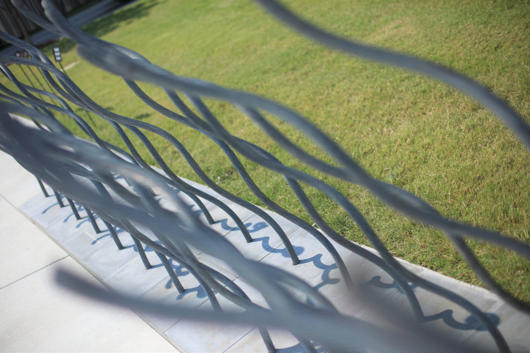 A sculpture of twisted wires rising out of pavers sits between a sidewalk and a lawn