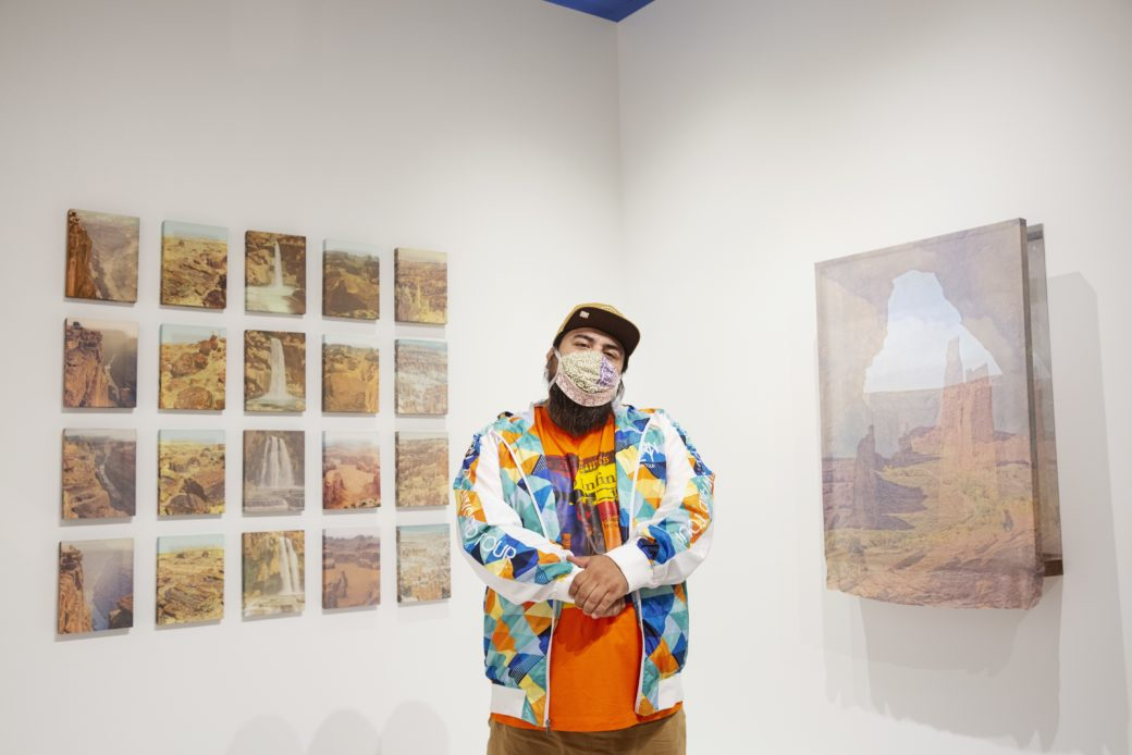 A masked figure in a baseball cap and vibrant clothing poses in front of artworks depicting western scenes