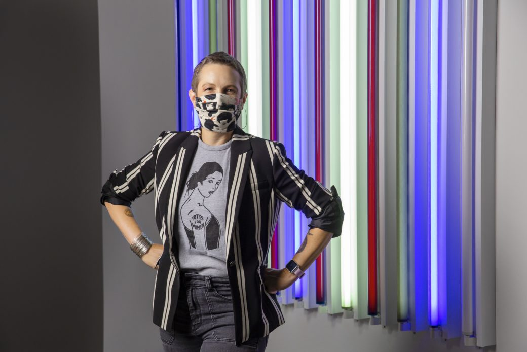 A masked figure with short hair poses in front of a light sculpture artwork