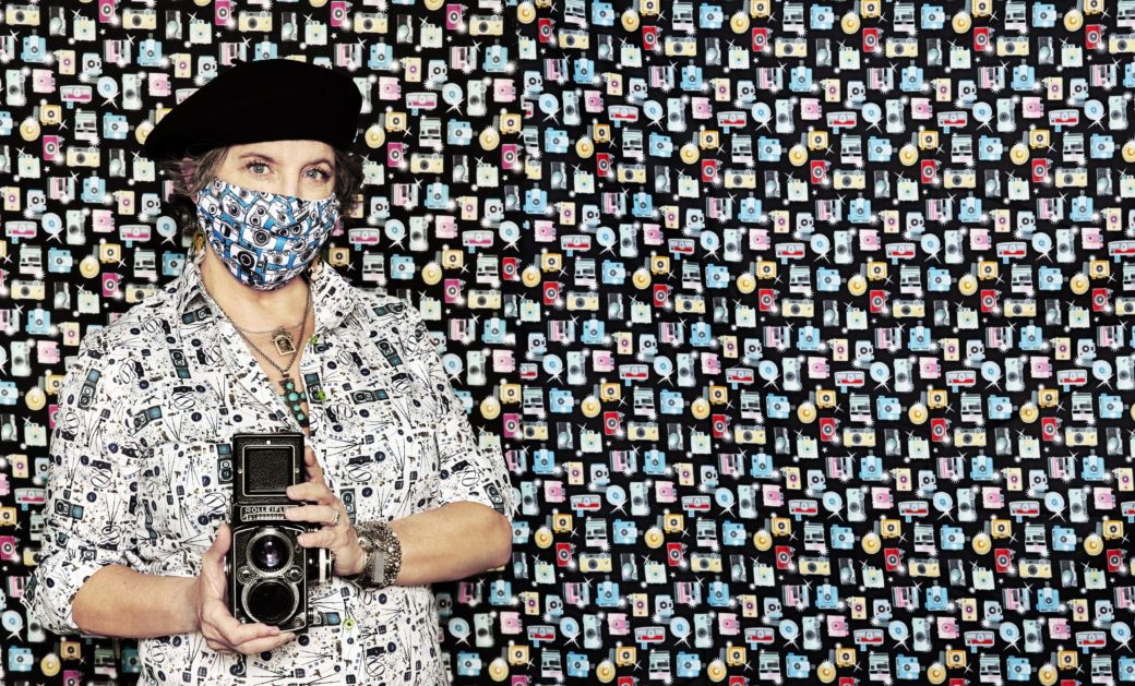 A masked figure holding a camera poses in front of a background resembling the mask pattern: vintage cameras