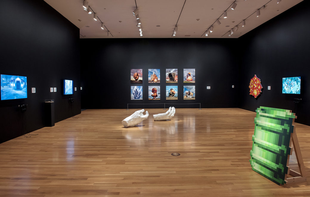 A gallery with polished wooden floors and black walls displays a 2-D sculpture of a green barrel with digital and traditional works on the walls