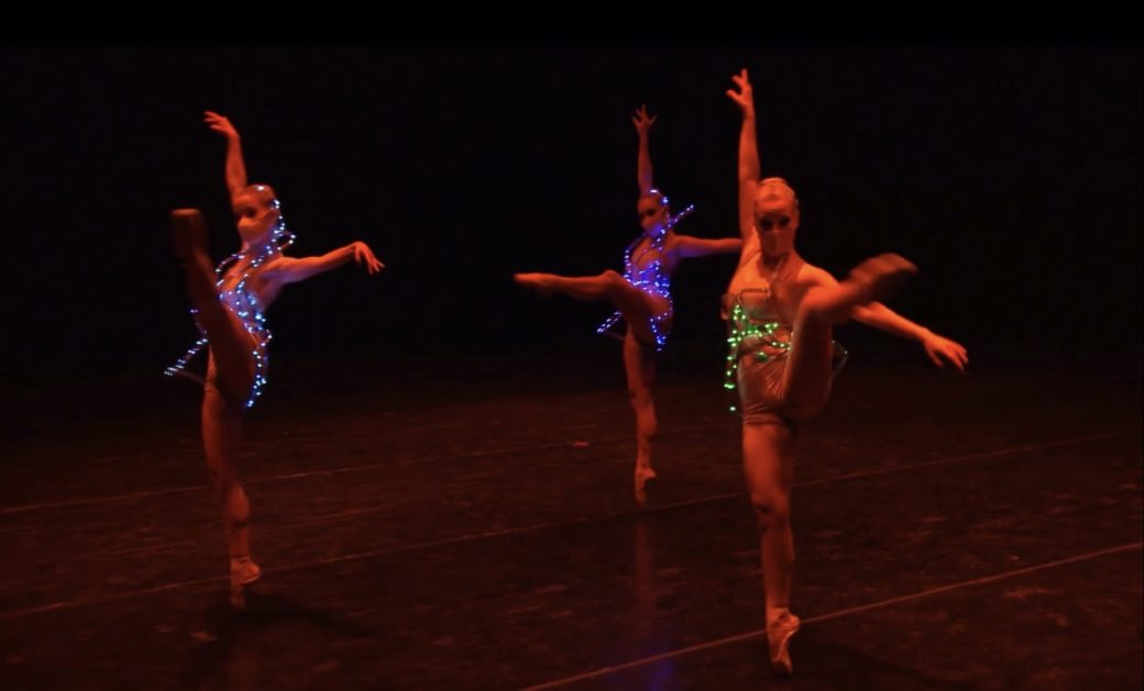 Three dancers perform in lighted, multicolored leotards beneath a dark red light.