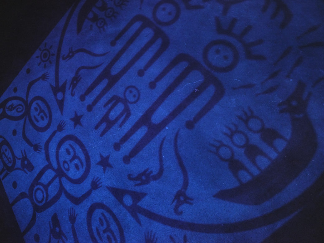 A detail photograph depicts pictoral representations of Indigenous myths, bathed in a soft blue light