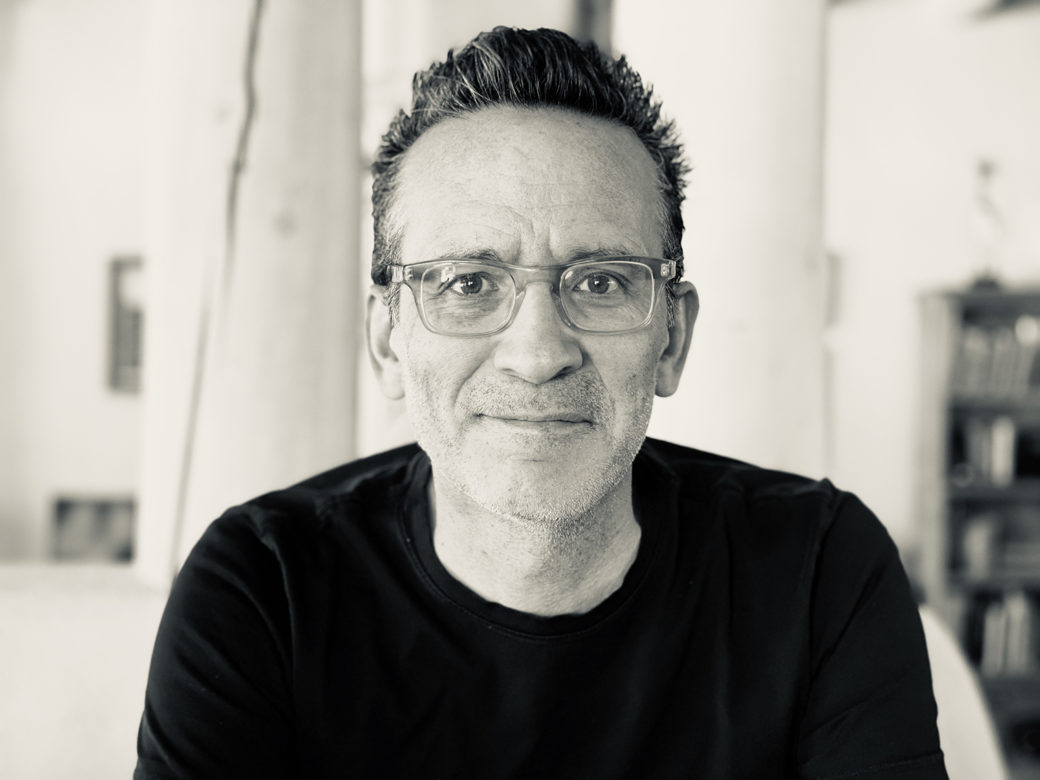 A biracial figure wearing a black shirt and glasses with clear frames smiles at the camera