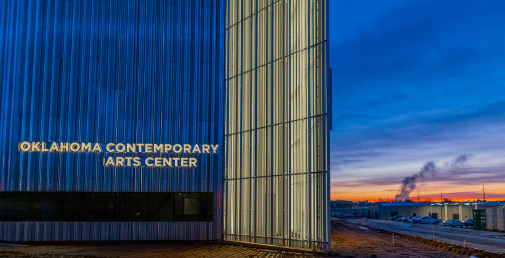 "Sunrise shows behind a silver building with the words ""Oklahoma Contemporary Arts Center"" illuminated"