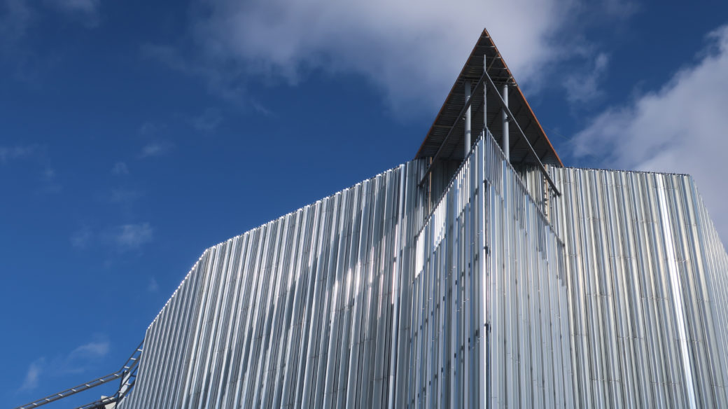 A silver building sits beneath a cloudy, blue sky