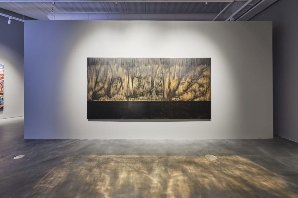 An abstract landscape, rendered in illuminating gold and black, hangs on the wall of an art gallery