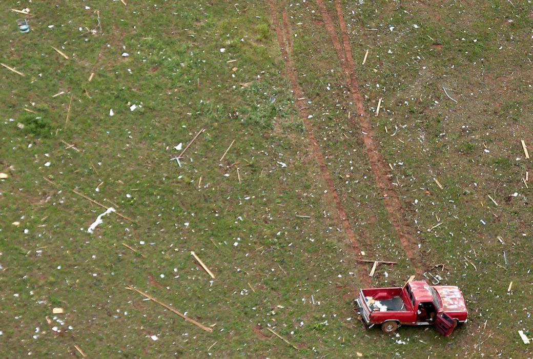 Damaged red truck in a field with debris from above