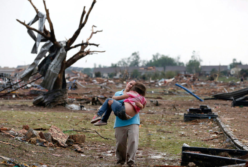 An adult carries a child away from the ruins of a neighborhood
