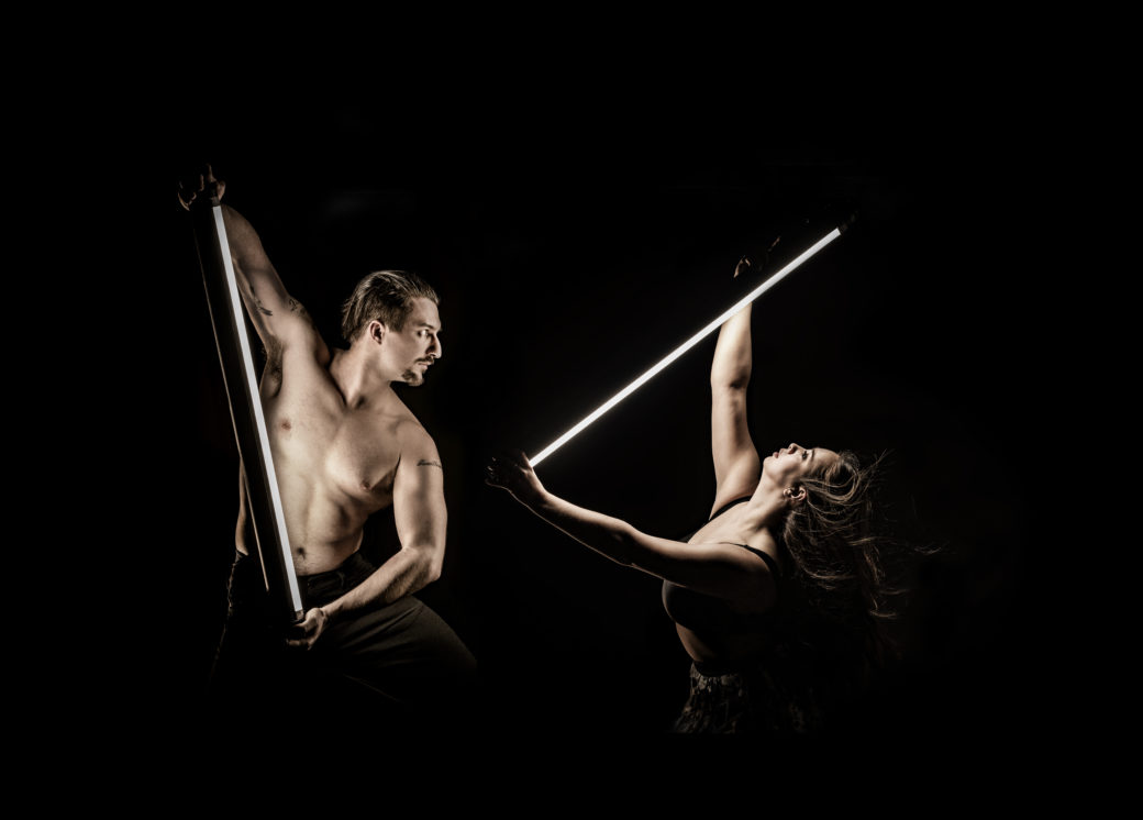 Two figures dance with portable lights against a black background