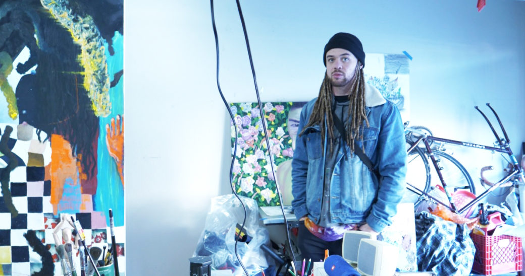 An artist in a blue jean jacket stands in a studio, surrounded by canvases and objects
