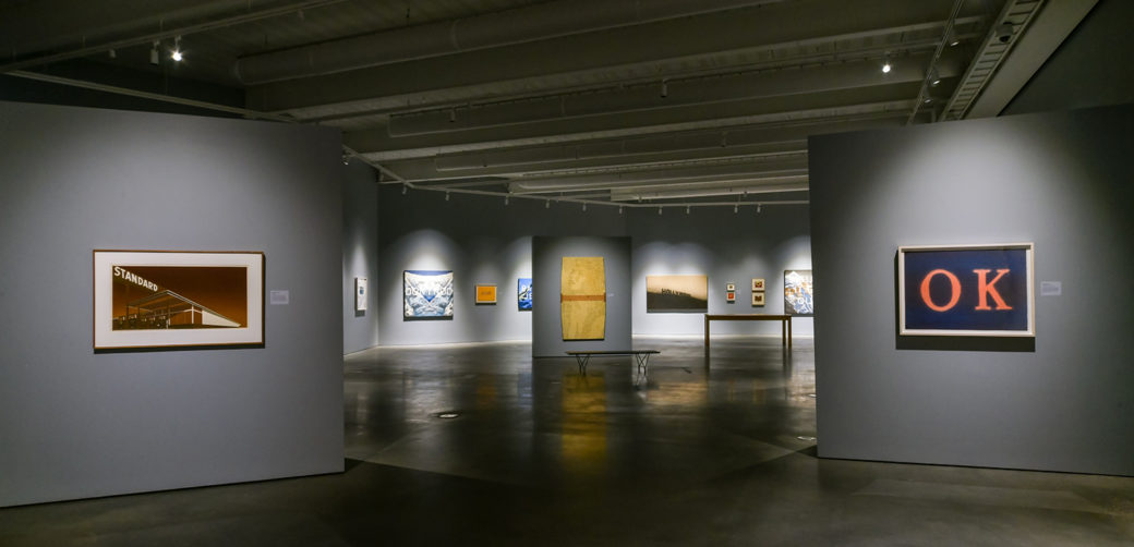 Wide view of an art gallery space with multiple paintings and prints hanging on walls throughout