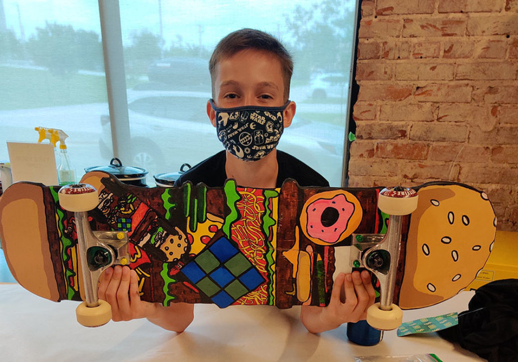 A child in a mask holds up a painted skateboard with window in the background