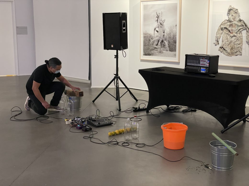 A man in a mask kneels on the floor of an art gallery amid a variety of objects, in front of a large speaker and a piece of music production equipment