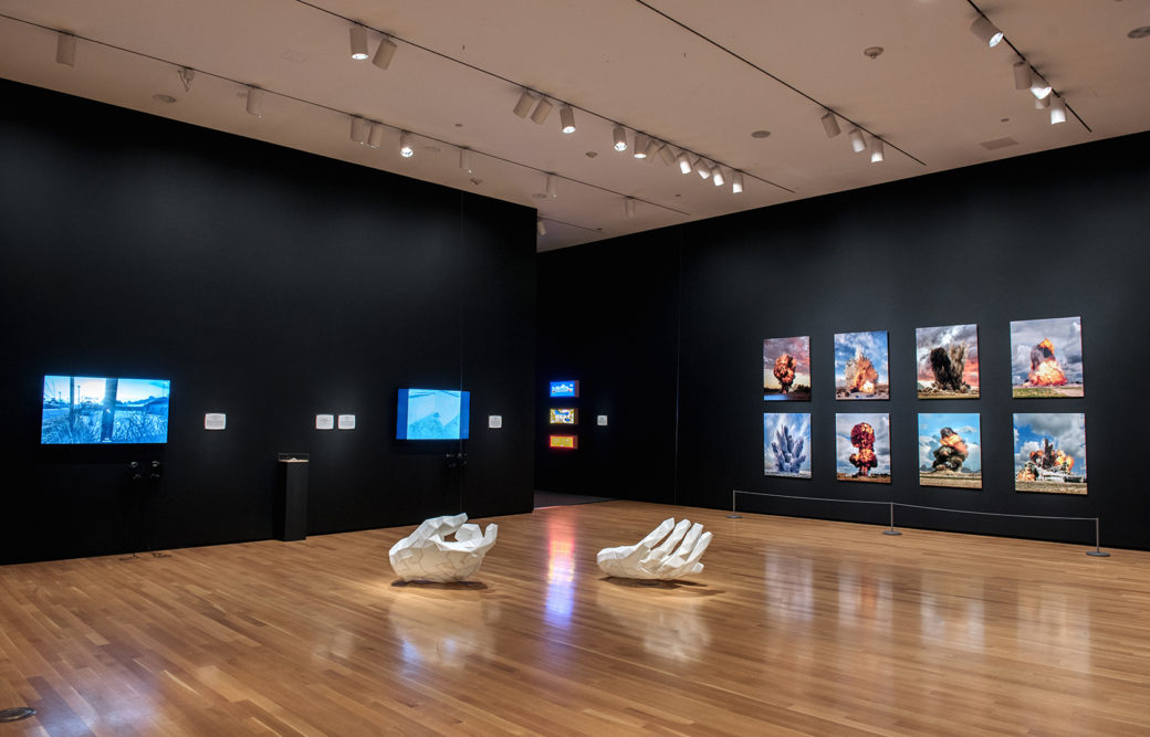 A pair of white, sculptural hands lay on a wood floor in a gallery with black walls featuring screens and artworks