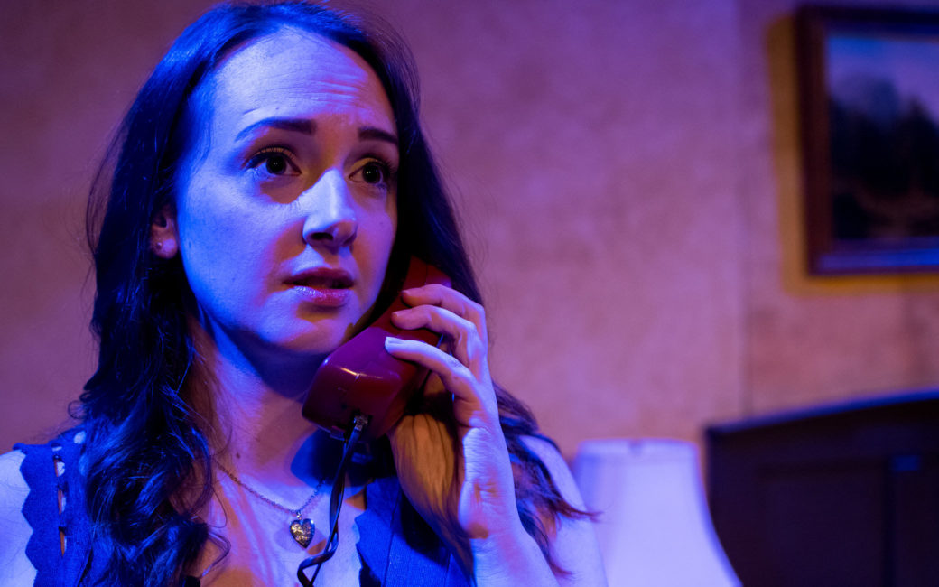 An adult immersed in blue stage light holds a red phone