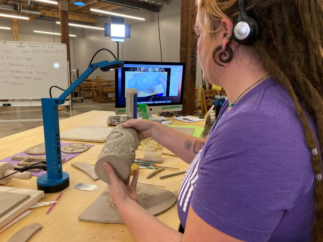 A person in a purple shirt examines a clay object under a blue lamp