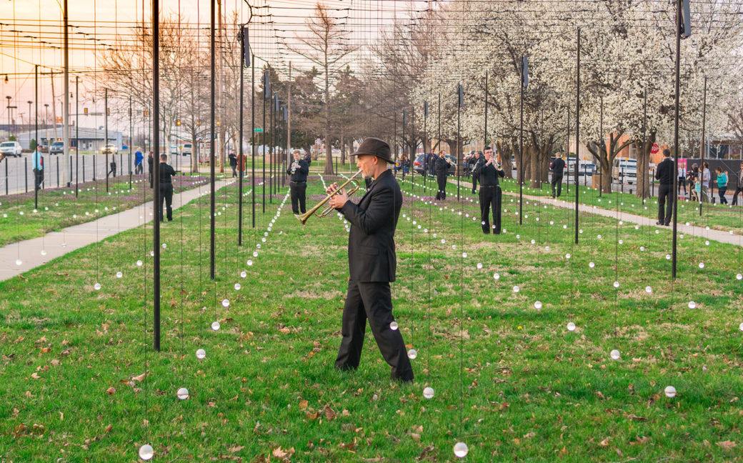 Trumpeters dressed in black play music in a park among a grid of dangling lights