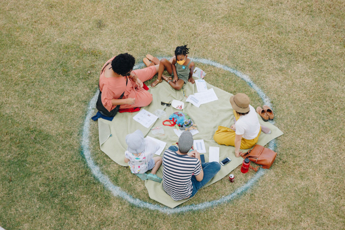 Three adults and a child sit inside a marked circle on a grassy field