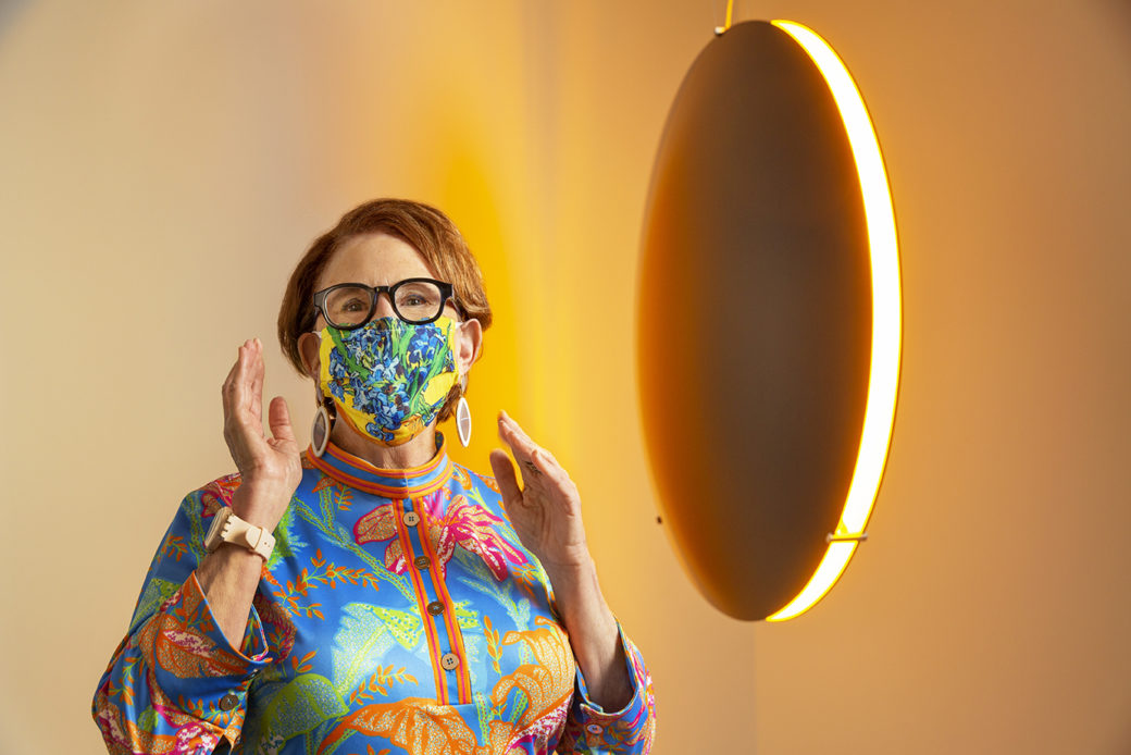 A woman in a colorful mask and blouse in front of a lighted disc sculpture