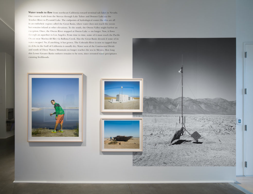 Photo depicts an art gallery with photos and text on a white wall