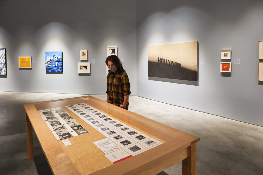 A figure in a plaid shirt and a mask looks at pages of an artist's books in a display table in a gallery