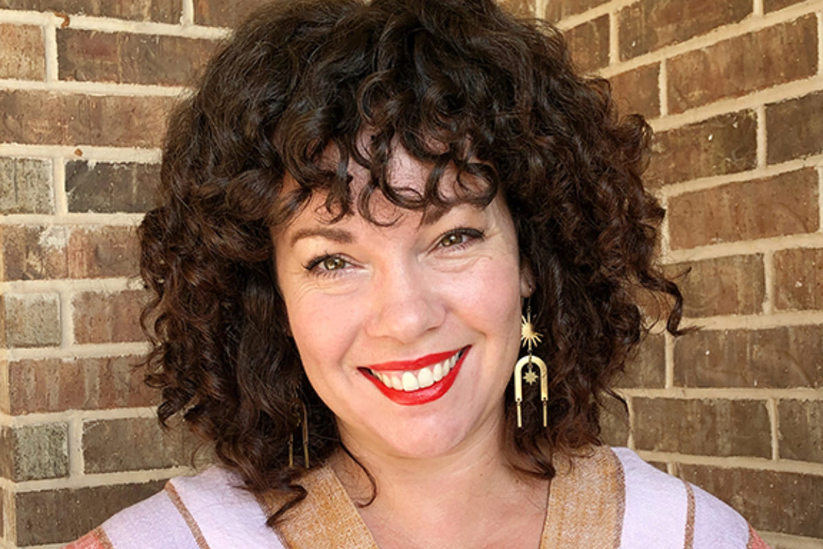 Woman with brown curly hair and red lipstick smiles at the camera against a brick backdrop.