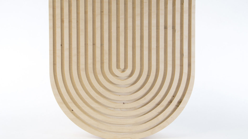 A U-shaped wooden sculpture features carved U-shaped grooves throughout