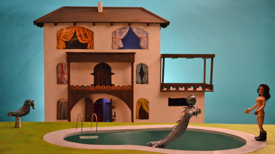 A still from stop-motion animation shows the front of a large house, where a doll figure reaches for a metallic mer-creature coming out of a pool