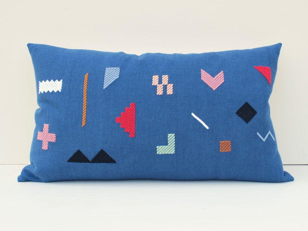A rectangular light blue pillow features embroidered shapes such as triangles, squares and arrows