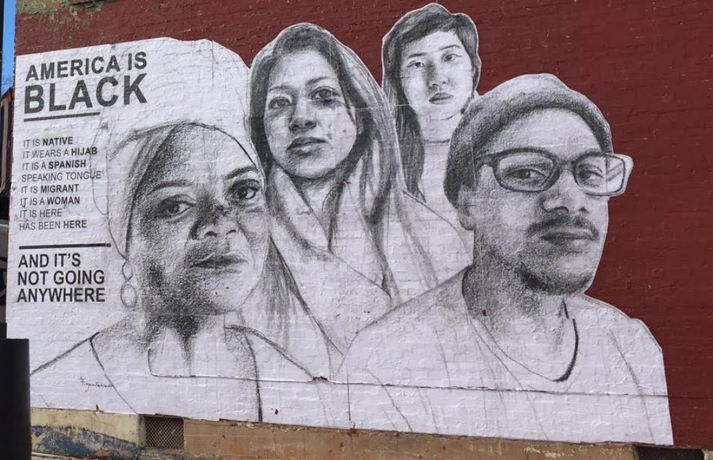 "A mural on a dark red wall shows four people of color next to the words ""AMERICA IS BLACK"""