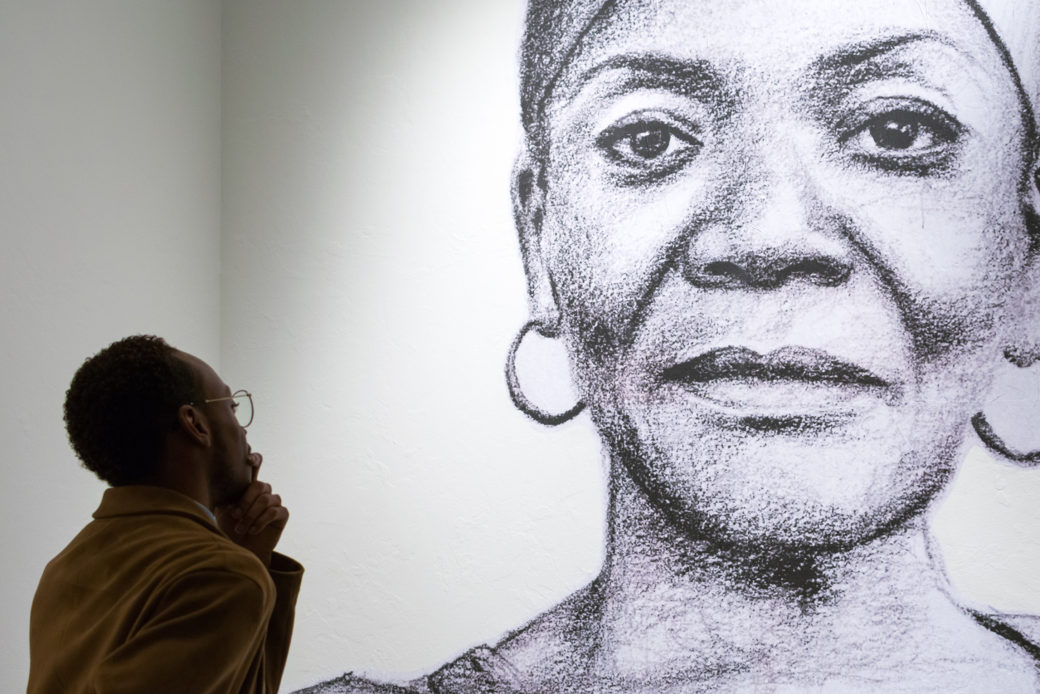 A dark-skinned man ponders a wall with a large sketch of a dark-skinned woman in hoop earrings